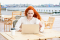 Redhead female looking at laptop in cafe outside - PhotoDune Item for Sale