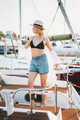 Beautiful sensitive blonde young woman in short and straw hats on the yacht at pier - PhotoDune Item for Sale