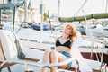 Beautiful sensitive blonde young woman in short and straw hats on yacht at pier - PhotoDune Item for Sale