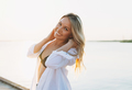 Beautiful blonde young woman in white shirt on pier on sunset - PhotoDune Item for Sale