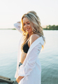 Beautiful smiling blonde young woman in white shirt on the beach on sunset - PhotoDune Item for Sale