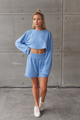 Young caucasian blonde in a fashionable sportswear look on woman. Blue shorts and sweatshirt. - PhotoDune Item for Sale