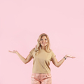 Caucasian blonde woman smiles and spreads her hands gesturing no idea isolated on pink background. - PhotoDune Item for Sale