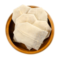 Tea bags, made of filter paper, with tea in a wooden bowl - PhotoDune Item for Sale