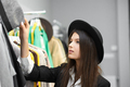Pretty girl trying on black hats in clothing shop - PhotoDune Item for Sale