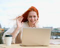 Cheerful redhead female chatting on laptop in cafe outside - PhotoDune Item for Sale