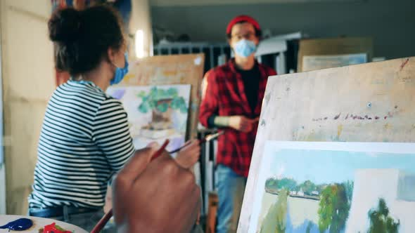 Students are Painting During Art Class with a Teacher in a Face Mask