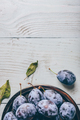 Plums on plate over wooden surface - PhotoDune Item for Sale