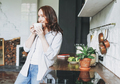 Adult smiling brunette woman in casual with cup of tea on kitchen at the home - PhotoDune Item for Sale