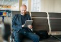 Handsome adult bald bearded man businessman in suit using tablet at airport lounge - PhotoDune Item for Sale