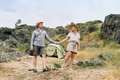 Happy young couple travelers in casual outfits with tent on mountain background - PhotoDune Item for Sale