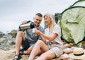 Young couple travelers in casual outfits with tent. Man pours tea from thermos - PhotoDune Item for Sale