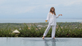 Gorgeous girl in white wistfully posing at the edge of pool on villa with beautiful view on island - PhotoDune Item for Sale