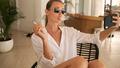 Posh stylish girl in sunglasses smoking cigarette taking selfie on phone in villa at tropical island - PhotoDune Item for Sale