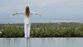 Back view of girl in sleepwear standing at the edge of swimming pool on villa with amazing view - PhotoDune Item for Sale