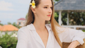 Beautiful girl with flower in hair dreamily looking away resting on terrace with amazing view - PhotoDune Item for Sale