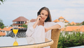 Beautiful girl in pajamas talking on smartphone while having breakfast on terrace with amazing view - PhotoDune Item for Sale