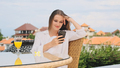 Beautiful girl in pajamas happily using smartphone resting on terrace with amazing view - PhotoDune Item for Sale