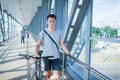 Handsome bicyclist standing on bridge - PhotoDune Item for Sale
