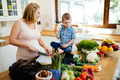 Pregnant woman preparing meal with son - PhotoDune Item for Sale