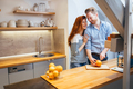 Couple making orange smoothie in kitchen - PhotoDune Item for Sale