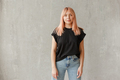 Young girl wearing blank black t-shirt. Concrete wall background. Horizontal - PhotoDune Item for Sale