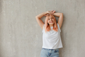 Young joyful woman in white t-shirt with dyed hair posing at wall with raised hands - PhotoDune Item for Sale
