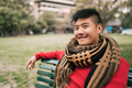 Asian man sitting on a bench in park. - PhotoDune Item for Sale