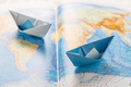 Paper boats on world map. Concept of traveling or military exercise. - PhotoDune Item for Sale