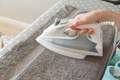 Hands with modern iron with steam system ironing clean, crumpled towel. - PhotoDune Item for Sale