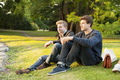 Full length of handsome men looking away while sitting on grassy field in park - PhotoDune Item for Sale