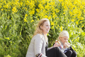 Happy woman looking away while having snacks with daughter at rapeseed field - PhotoDune Item for Sale