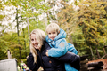 Happy mother piggybacking son in park during autumn - PhotoDune Item for Sale