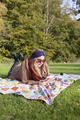 Full length of young woman reading novel while lying on picnic blanket at forest - PhotoDune Item for Sale