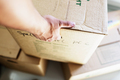 Cropped image of man's hand picking up cardboard box at new home - PhotoDune Item for Sale