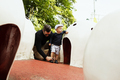 Father assisting son in wearing footwear by artificial igloos in park - PhotoDune Item for Sale
