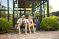Full length of happy father and son sitting outside house - PhotoDune Item for Sale