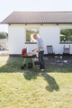 Full length of man grilling food outside house - PhotoDune Item for Sale