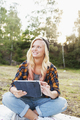 Smiling woman holding digital tablet while sitting on picnic blanket on field - PhotoDune Item for Sale