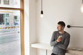Thoughtful man holding coffee cup while leaning on counter in coffee shop - PhotoDune Item for Sale