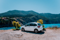 Vacation travel with car concept. Rental hired car in front of amazing bay with turquoise water - PhotoDune Item for Sale