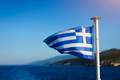 Flag of Greece waving over the see on cruise sheep in front of beautiful coastline - PhotoDune Item for Sale