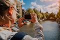 Woman tourist taking a picture of canal in Amsterdam on the mobile phone. Warm gold afternoon - PhotoDune Item for Sale