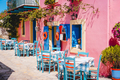 Traditional greek vivid lilac colored tavern on the narrow Mediterranean street on hot summer day - PhotoDune Item for Sale