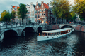 Beautiful view of Amsterdam canals with white cruise boat bridge and typical dutch houses. Holland - PhotoDune Item for Sale