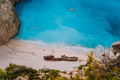 Shipwreck on Navagio beach. Azure turquoise sea water and paradise sandy beach in evening light - PhotoDune Item for Sale