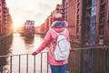 Rear view of adult woman tourist with backpack enjoying sunset on the bridge in Speicherstadt - PhotoDune Item for Sale