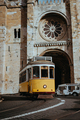 Quaint yellow tram passes directly in front of the Se Cathedral in Lisbon. Lisboa Lissabon - PhotoDune Item for Sale