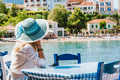 Rear view of tourist woman sitting in a cafe wear blue sunhat enjoying colorful tranquil houses of - PhotoDune Item for Sale