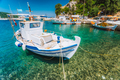 Traditional fishing boat in crystal clear Mediterranean sea cove of Ithaka island, Greece - PhotoDune Item for Sale